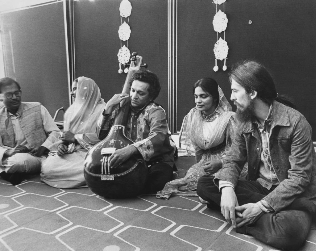 British musician George Harrison of the Beatles (1943 - 2001, right) with a company of seven top Indian instrumentalists, singers and dancers, including Ravi Shankar (centre, on sitar) at a press reception at the Royal Festival Hall in London | Getty Images / Global Images Ukraine