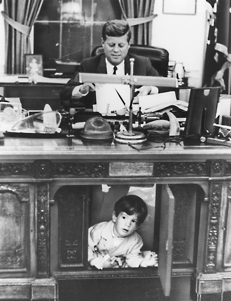 John F. Kennedy Jr. hides under his father's desk circa 1963. | Source: Wikimedia Commons