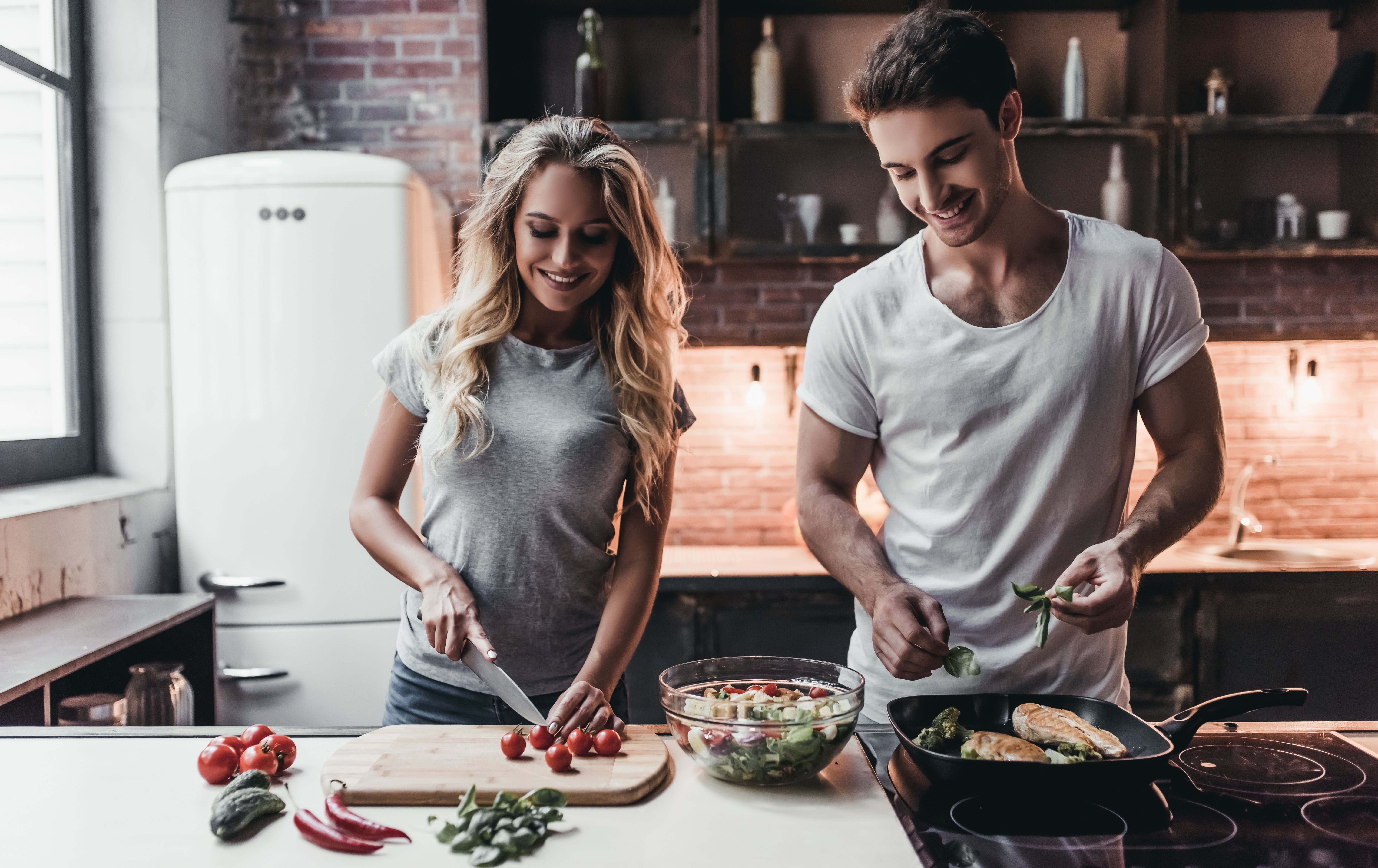 A couple happily cooking together. │ Source: Shutterstock