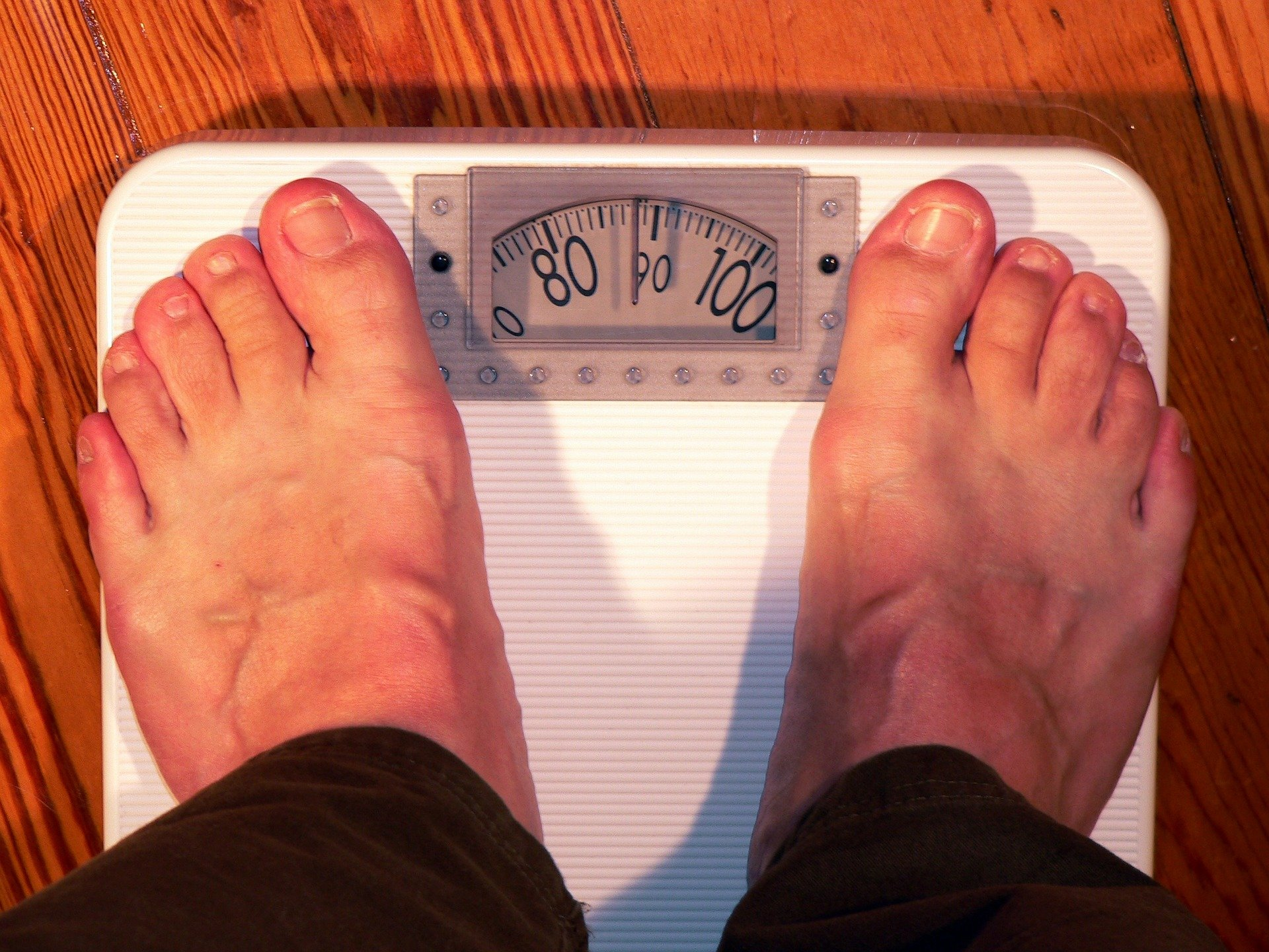 A man on a scale checking out his weight | Photo: Pixabay