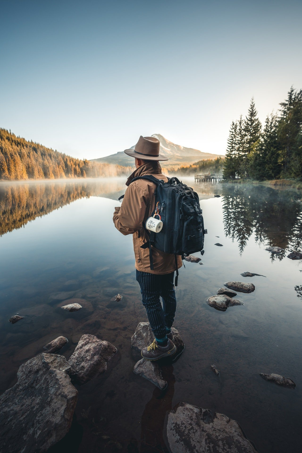 Photo of a man in a brown jacket standing on a rock   Photo: Pexels