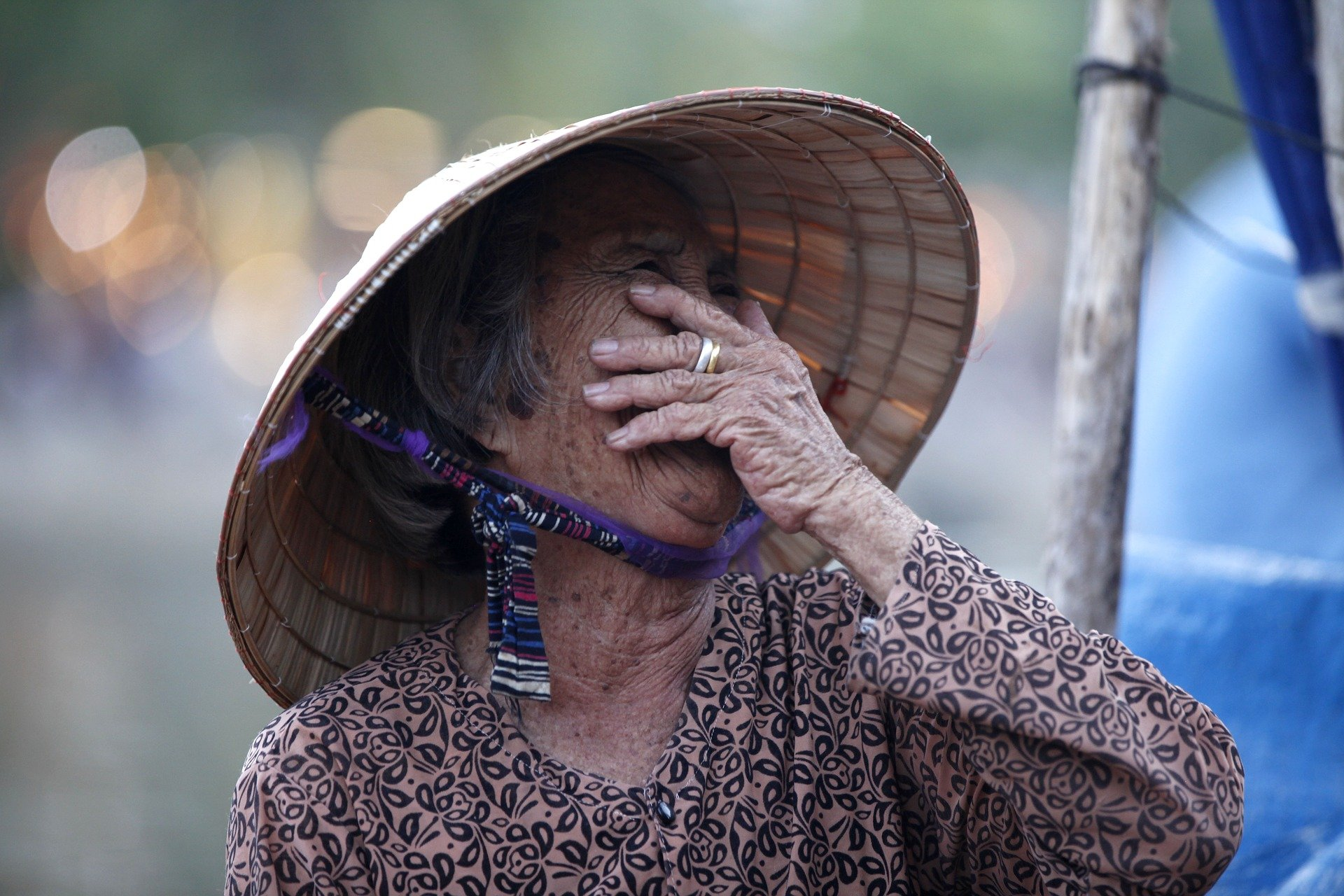 An old woman wearing a hat, covering her mouth while laughing | Photo: Pixabay/Thangphan