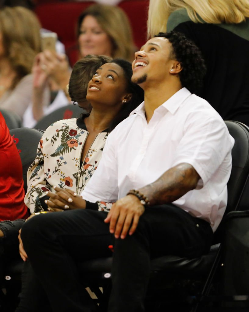 imone Biles and Stacey Ervin watch the game between the Houston Rockets and the Utah Jazz ,2017| Photo: Getty Images