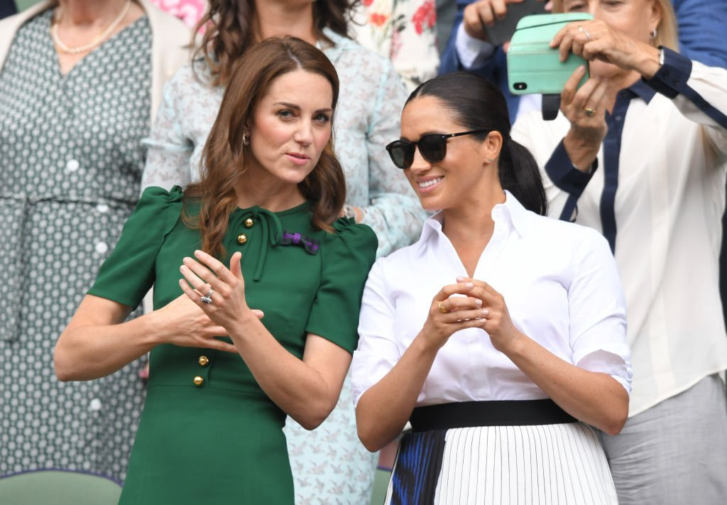 Kate Middleton and Meghan Markle chat while standing in the Royal Box on Centre Court during the Wimbledon Tennis Championships on July 13, 2019, in London, England | Source: Karwai Tang/Getty Images