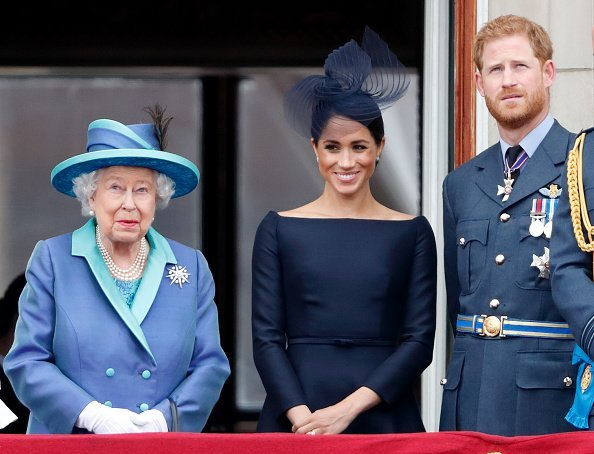 Queen Elizabeth II, Meghan, Duchess of Sussex and Prince Harry, Duke of Sussex watch a flypast to mark the centenary of the Royal Air Force from the balcony of Buckingham Palace on July 10, 2018 in London, England.| Photo:Getty Images