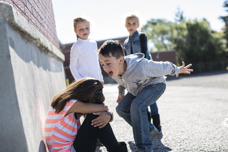 Niña triste siendo víctima de bullying escolar en medio del recreo. Fuente: Shutterstock
