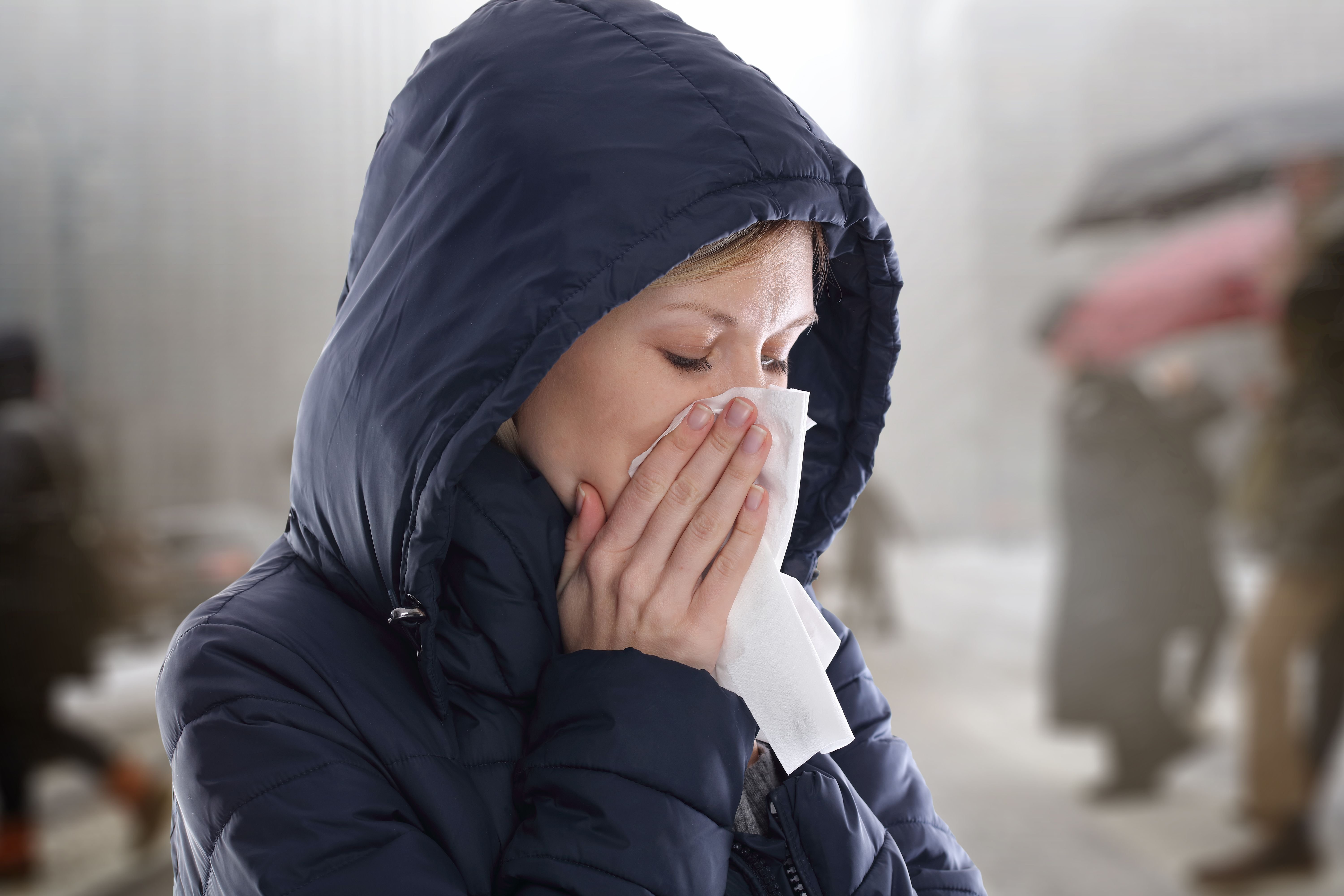 A sick woman blows her nose on tissue. | Source: Shutterstock