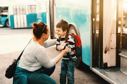 A mother talking to her son before the board a bus. | Source: Shutterstock.
