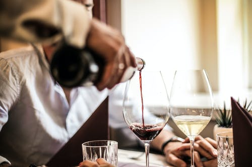 A waiter pouring wine into wine cups. | Photo: Pexel