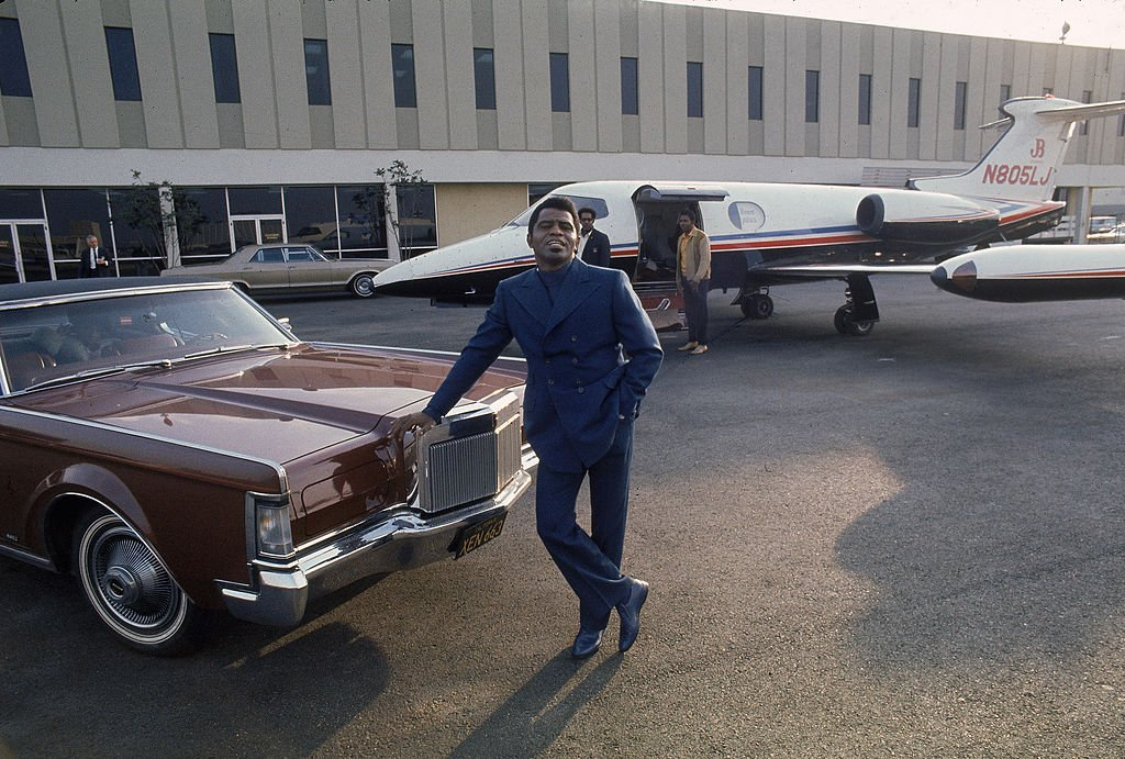 James Brown leans on the hood of a 1970 Lincoln Continental Mark III Coupe car parked in front of a Learjet 24A airplane at Los Angeles International Airport, 1969. | Photo: Getty Images