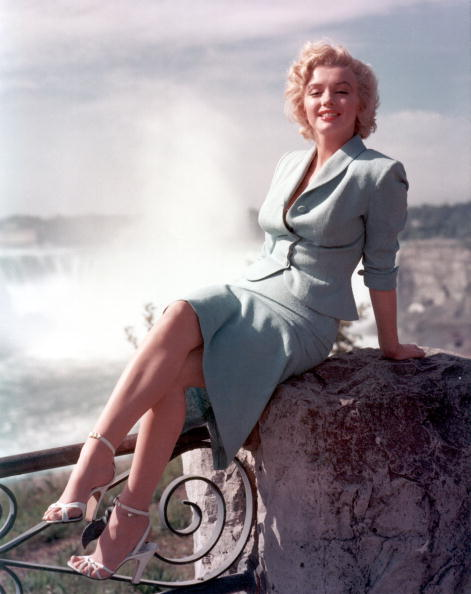 "Actress Marilyn Monroe poses for a portrait in front of Niagara Falls dressed as Rose Loomis from the film ""Niagara"" 