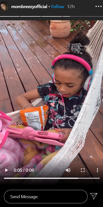A picture of Royalty relaxing in a hammock while using her tab. | Photo: Instagram/Mombreezyofficial