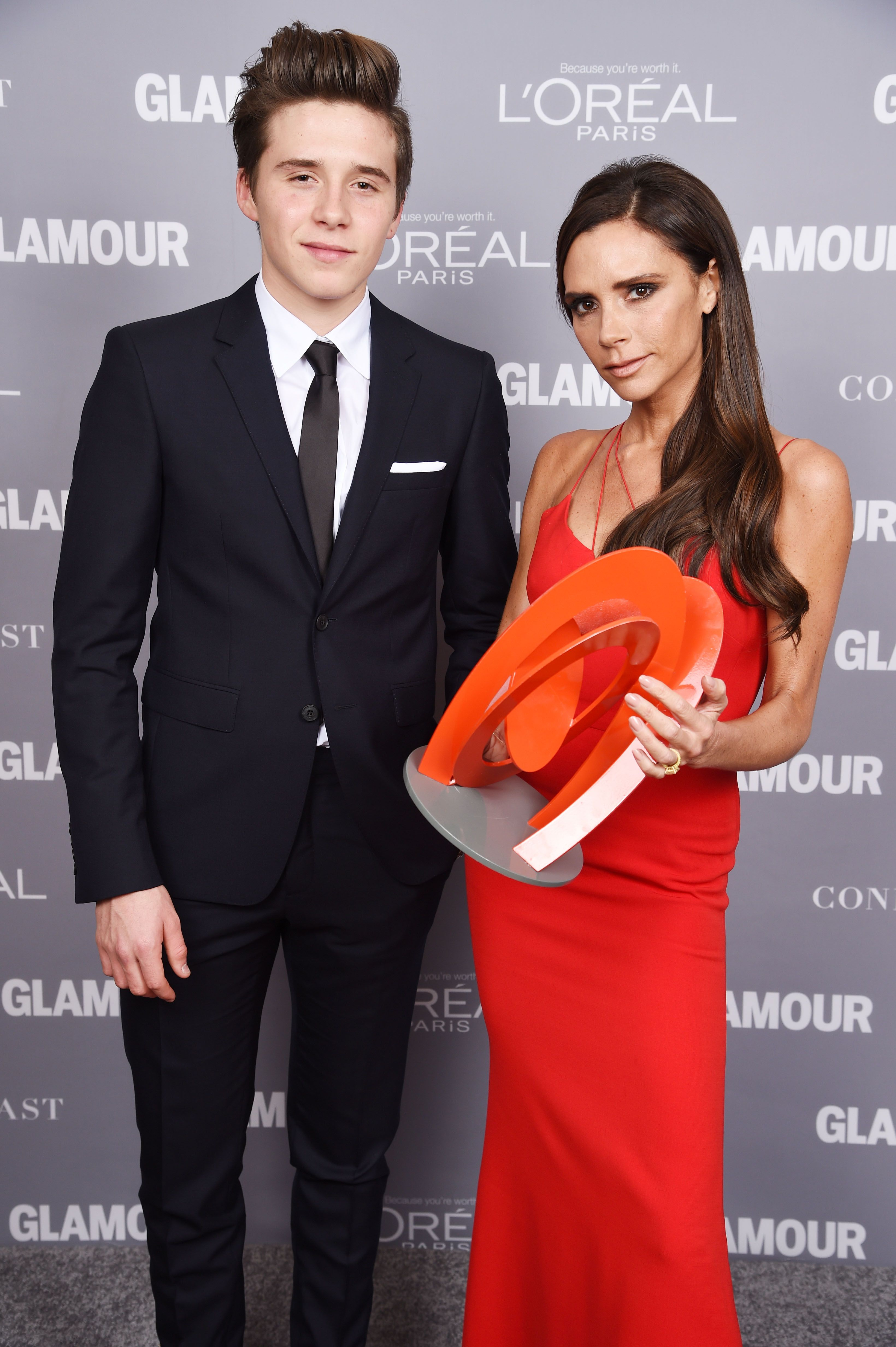Brooklyn Beckham (L) and designer Victoria Beckham pose backstage with her award at the 2015 Glamour Women Of The Year Awards at Carnegie Hall on November 9, 2015 in New York City. | Source: Getty Images