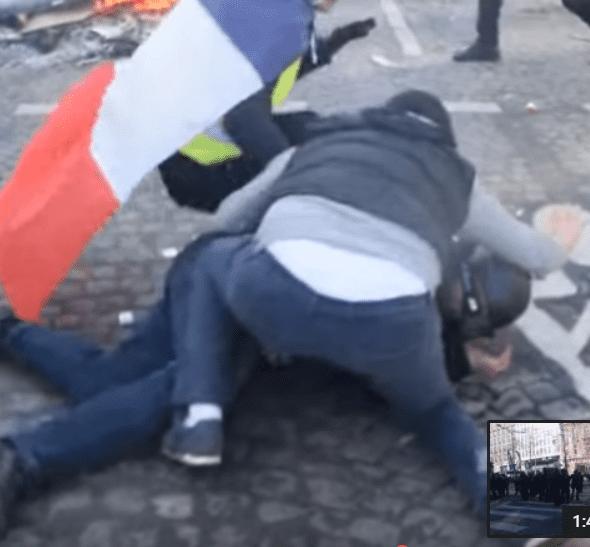 Adel et un Gilet jaune protégeant un policier sur les Champs-Elysées, le 16 mars 2019. | Photo : Youtube/InfoCritiqueWeb