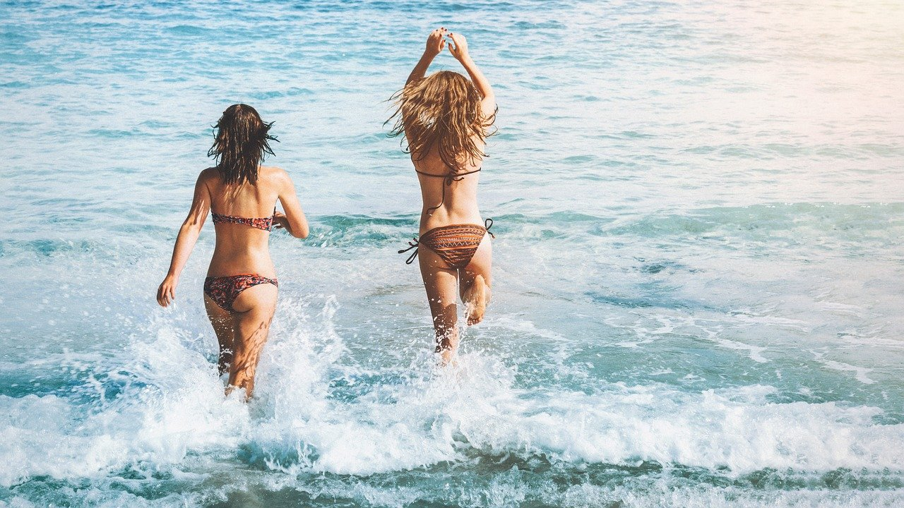 A picture of two women going into the ocean. | Photo: Pixabay