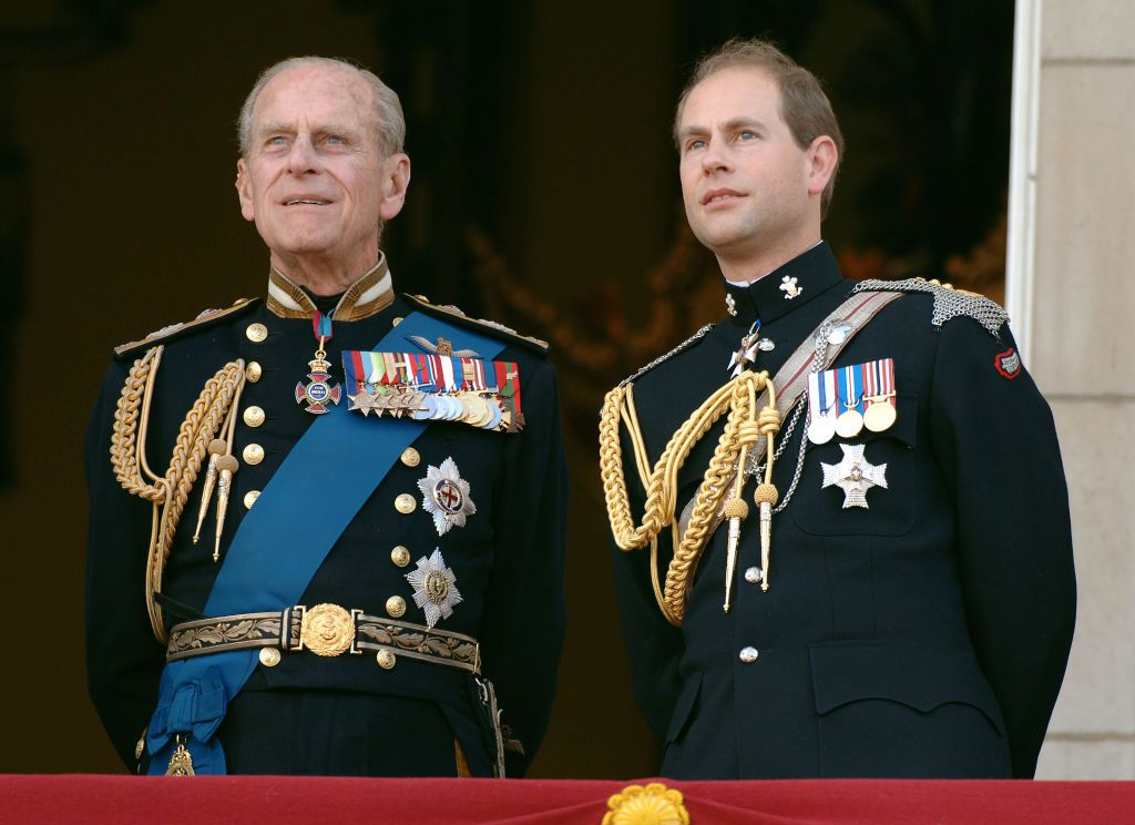Prince Edward, Earl of Wessex and his father, Prince Philp, Duke of Edinburgh watching the flypast over the Mall of British and US World War II aircraft from Buckingham Palace on National Commemoration Day in London, England | Photo: Anwar Hussein/Getty Images