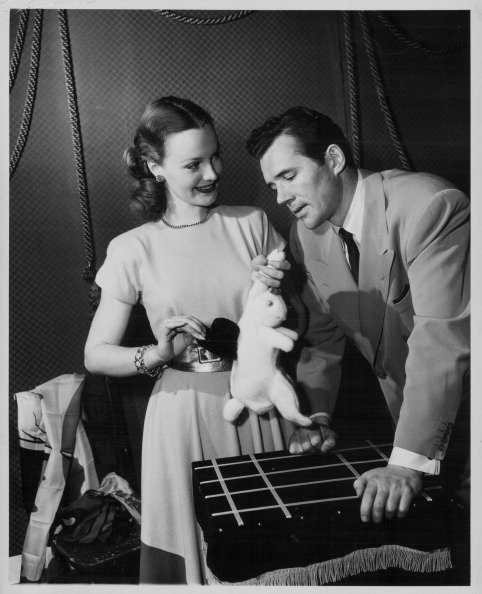 Dorothy Hart and Howard Duff, practicing a magic trick with a rabbit and a hat, circa 1945. | Source: Getty Images.