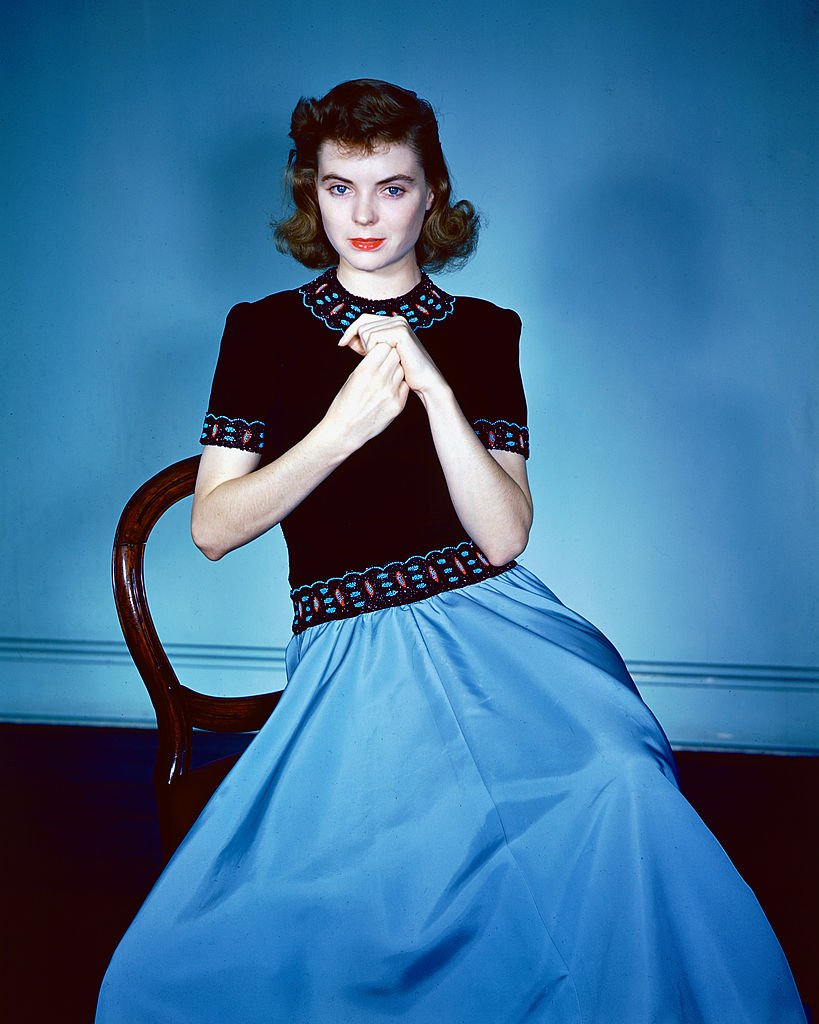 Dorothy McGuire (1916-2001) sitting on a chair, wearing a black top with red and blue trim and a blue skirt in a studio portrait, circa 1940.   Photo: Getty Images