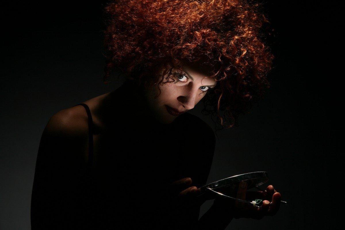 Mujer en la oscuridad con mirada intensa y espejo de mano. | Imagen: PxHere