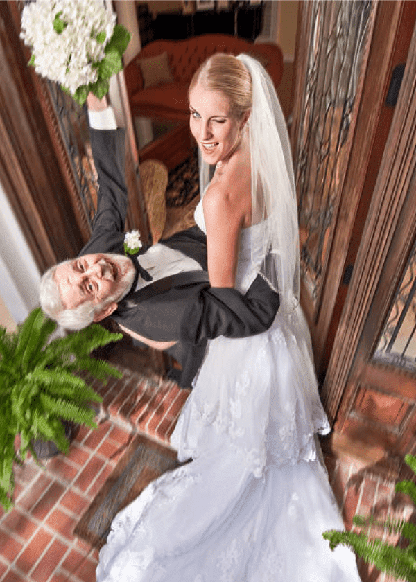 After their wedding, a young bride winking, carries older groom into their house | Source: Getty Images