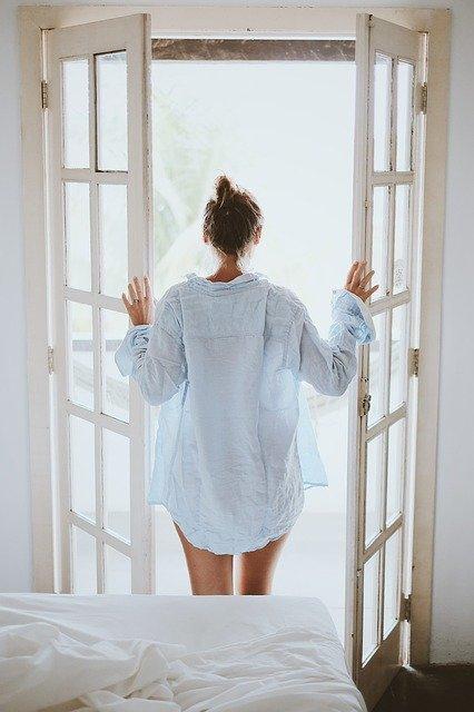 Mujer viendo hacia afuera desde el dormitorio. |Imagen:  Pixabay