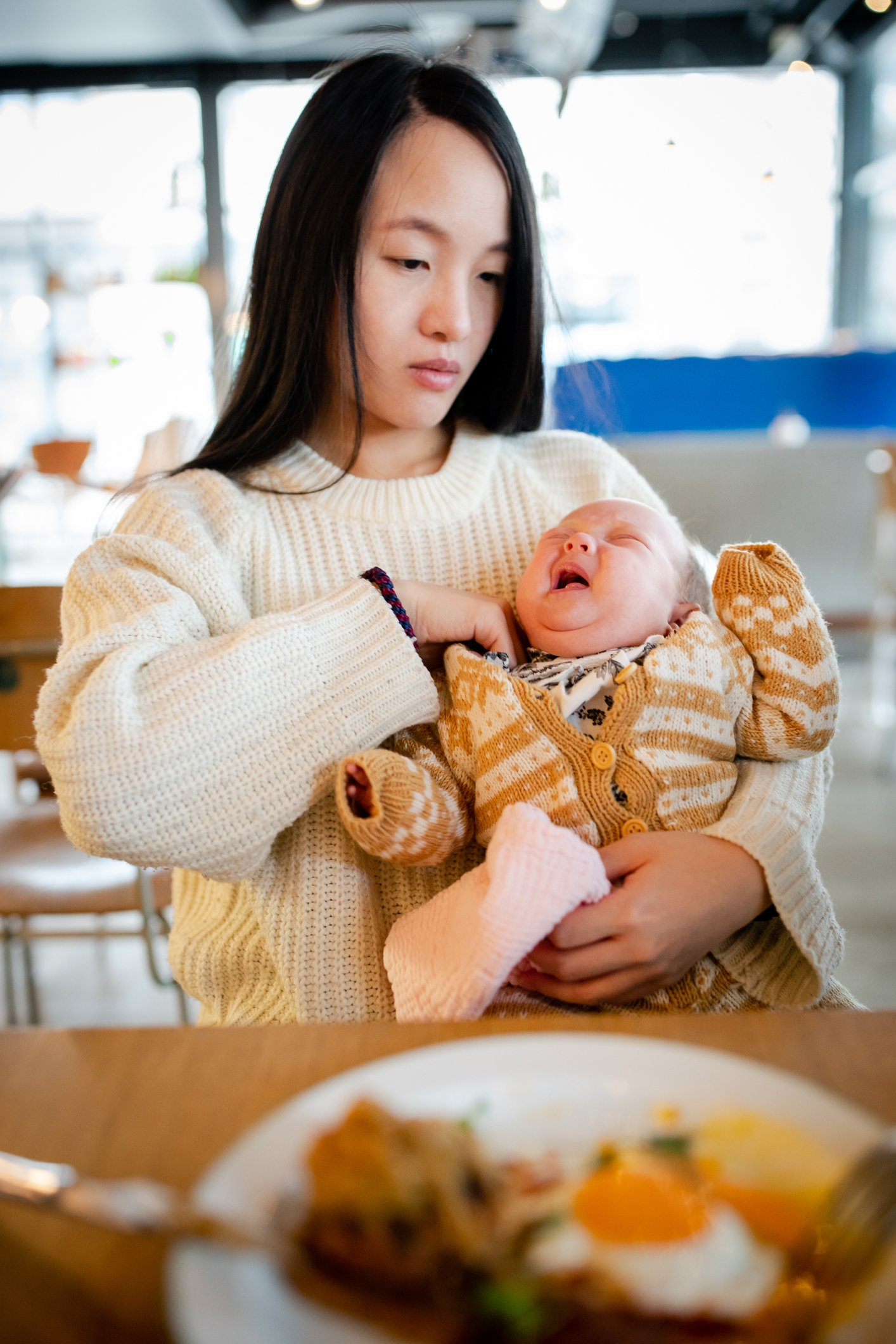 Mother holds her baby in a café | Photo: Getty Images
