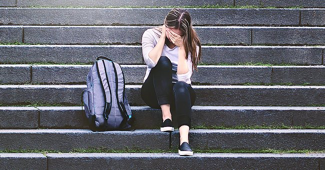 A teenage girl crying on the stairs | Photo: Shutterstock