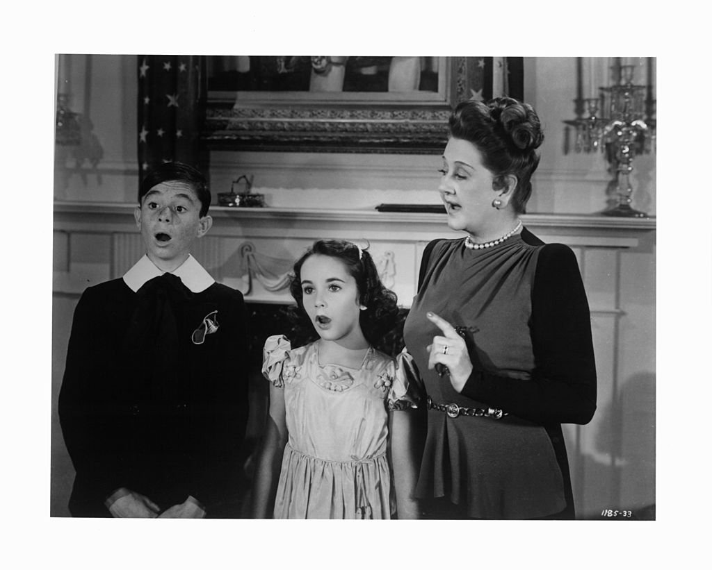 """Carl Alfalfa Switzer and Elizabeth Taylor led in song by Catherine Doucet in a scene from the film """"There's One Born Every Minute"""" circa 1942. 