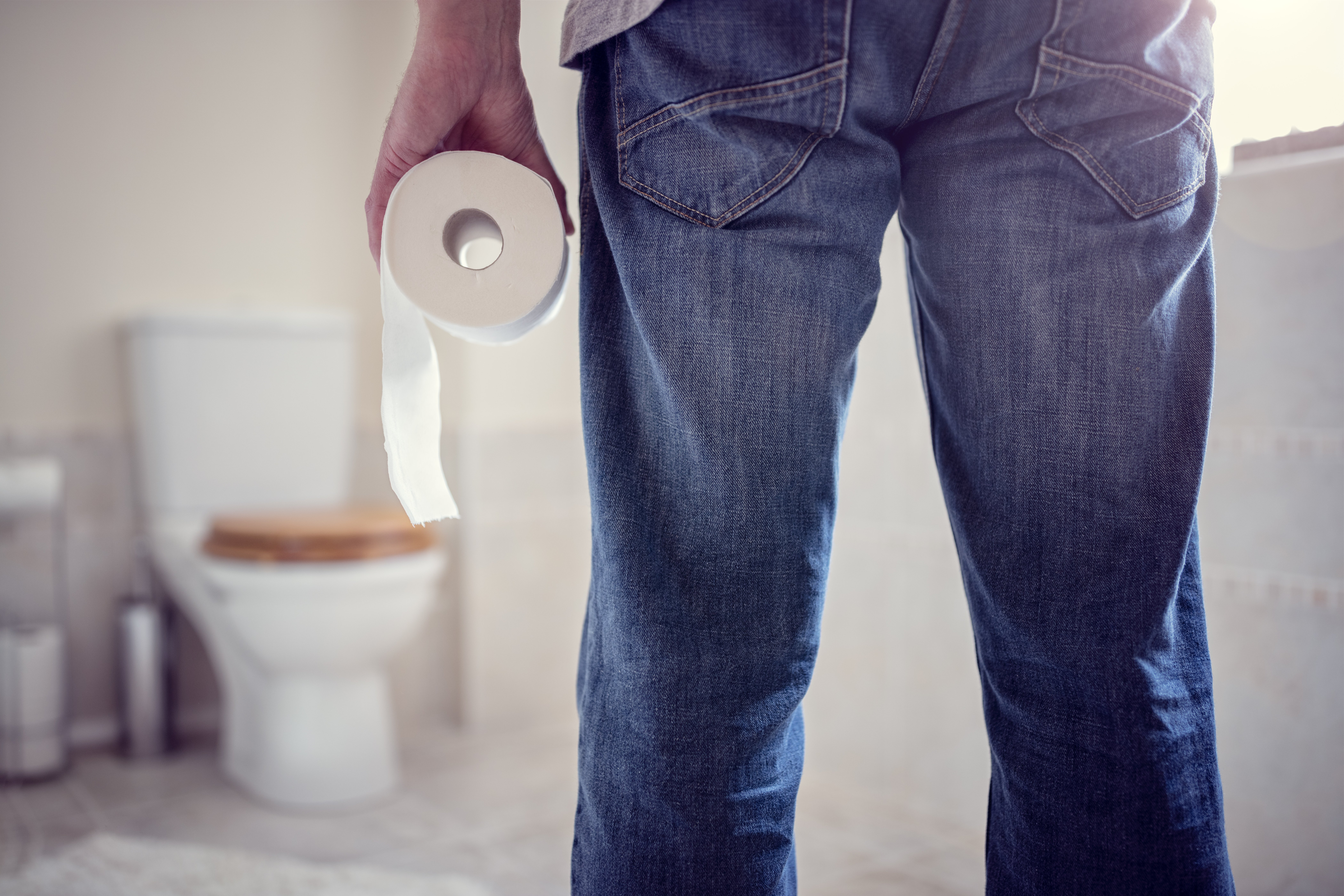 Man standing in front of a toilet with a roll of toilet paper in hand   Source: Shutterstock