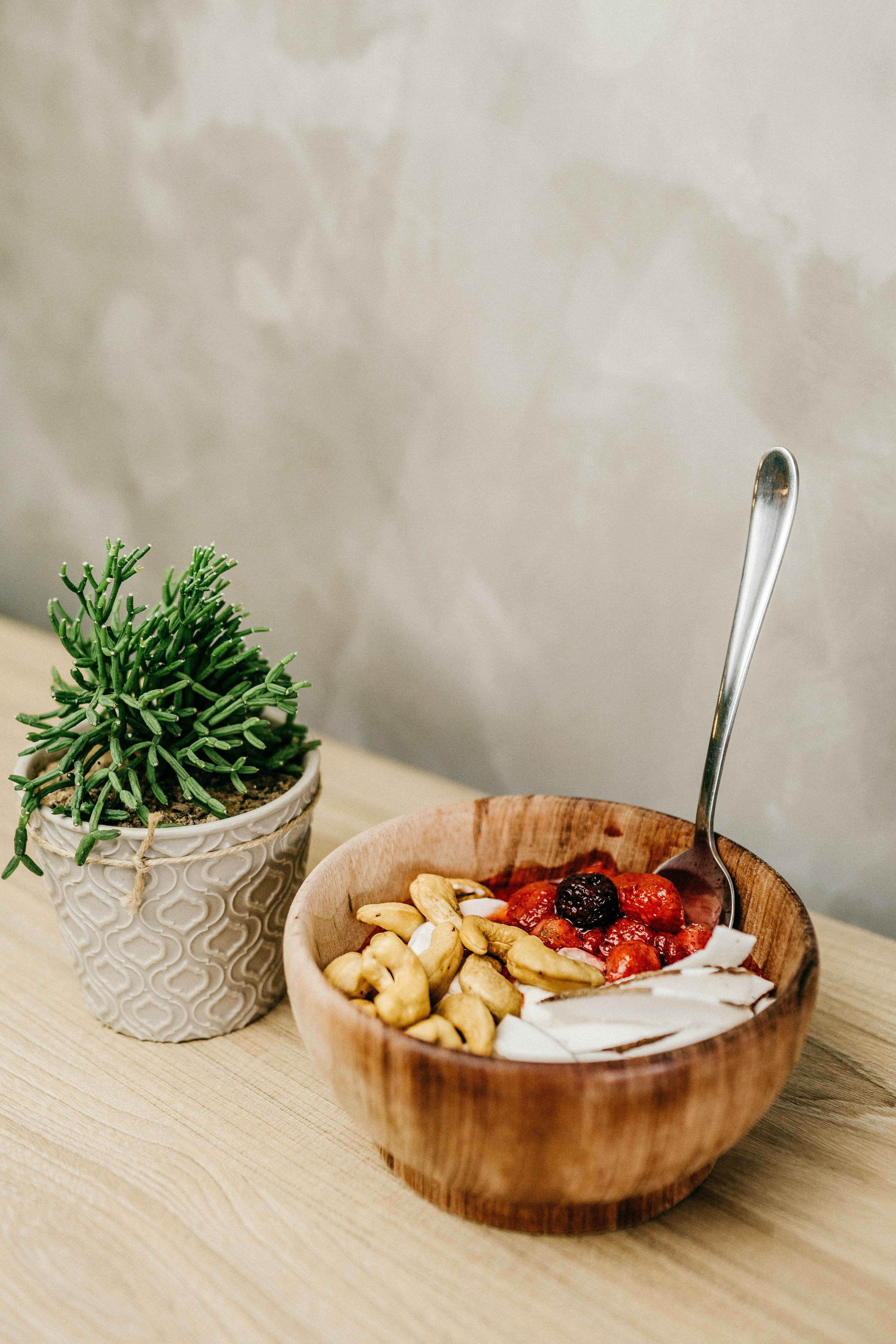 A photo of sliced berries and cashews in a wooden bowl   Source: Pexels