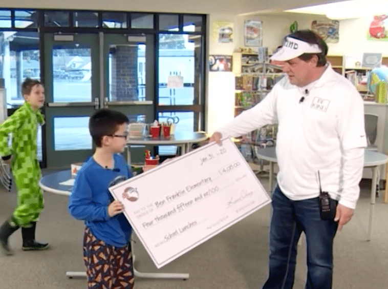 Keoni Ching hands out the check worth $4015 to his school to clear the lunch debt. | Source: YouTube/CBS 17