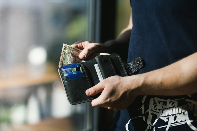 Person putting money in wallet | Photo: Pexels